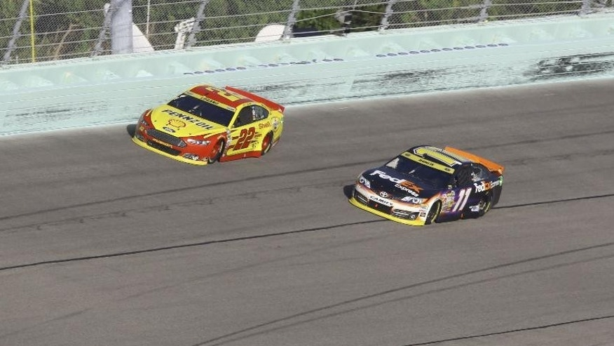 Joey Logano (22) and Denny Hamlin (11) compete during the NASCAR Sprint Cup championship series auto race, Sunday, Nov. 16, 2014, in Homestead, Fla. (AP Photo/David Graham)