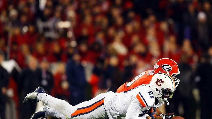 Auburn defensive back Robenson Therezie (27) breaks up a pass intended for Georgia wide receiver Kenneth Towns (9) in the first half of an NCAA college football game Saturday, Nov. 15, 2014, in Athens, Ga. (AP Photo/John Bazemore)