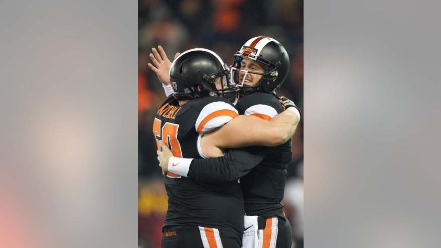 Oregon State quarterback Sean Mannion (4), right, celebrates with center Josh Mitchell (60) as the clock runs down during an NCAA college football game against Arizona State in Corvallis, Or., Saturday, Nov. 15, 2014. The Beavers beat the Sun Devils 35-27. (AP Photo/Troy Wayrynen)