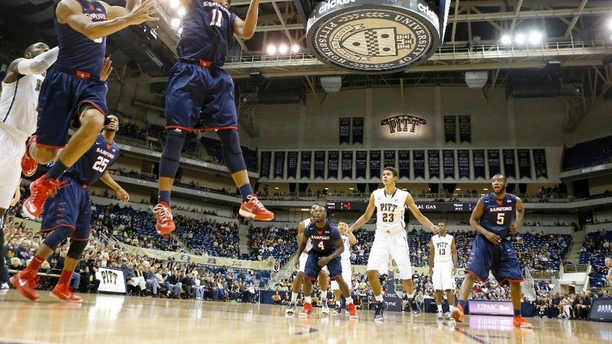 Samford's Evan Taylor (11) and Jamal Shabazz go after a rebound in front of Pittsburgh's Michael Young, left, in the first half of an NCAA college basketball game on Sunday, Nov. 16, 2014, in Pittsburgh. (AP Photo/Keith Srakocic)