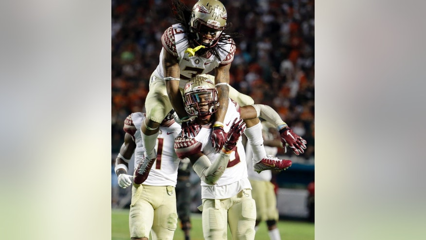 Florida State cornerback Ronald Darby (3) jumps onto defensive back Jalen Ramsey after Ramsey had a game ending interception in an NCAA college football game against Miami, Saturday, Nov. 15, 2014, in Miami Gardens, Fla. Florida State defeated Miami 30-26. (AP Photo/Lynne Sladky)