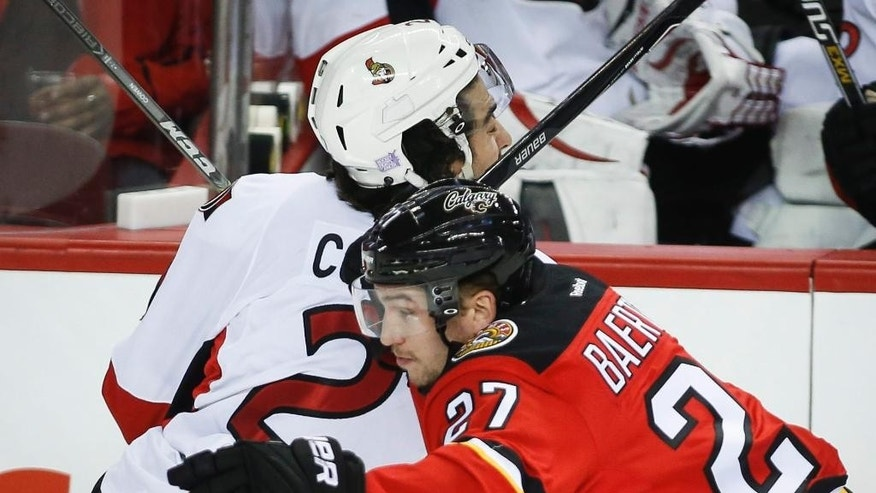 Ottawa Senators' Jared Cowen, left, takes a high stick in the face from Calgary Flames' Sven Baertschi, from Switzerland, during the first period of their NHL hockey game in Calgary on Saturday, Nov. 15, 2014. (AP Photo/The Canadian Press, Jeff McIntosh)