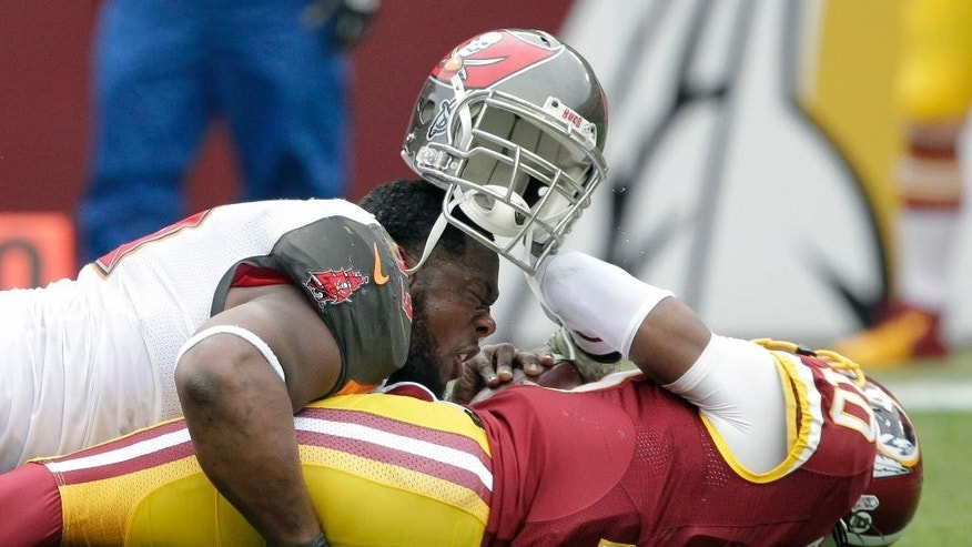 Tampa Bay Buccaneers defensive tackle Gerald McCoy, top, loses his helmet as he sacks Washington Redskins quarterback Robert Griffin III (10) during the first half of an NFL football game in Landover, Md., Sunday, Nov. 16, 2014. (AP Photo/Mark Tenally)