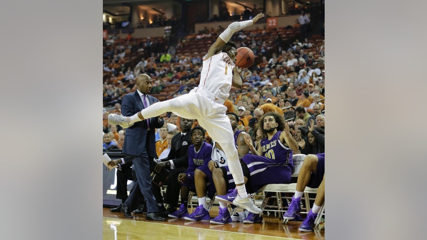 Texas' Isaiah Taylor (1) leaps towards the Alcorn State bench in pursuit of the ball during the first half of an NCAA college basketball game, Sunday, Nov. 16, 2014, in Austin, Texas. (AP Photo/Eric Gay)