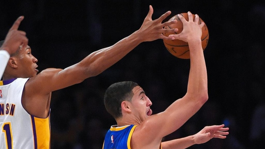Golden State Warriors guard Klay Thompson, right, goes up for a shot as Los Angeles Lakers forward Wesley Johnson defends during the first half of an NBA basketball game, Sunday, Nov. 16, 2014, in Los Angeles. (AP Photo/Mark J. Terrill)