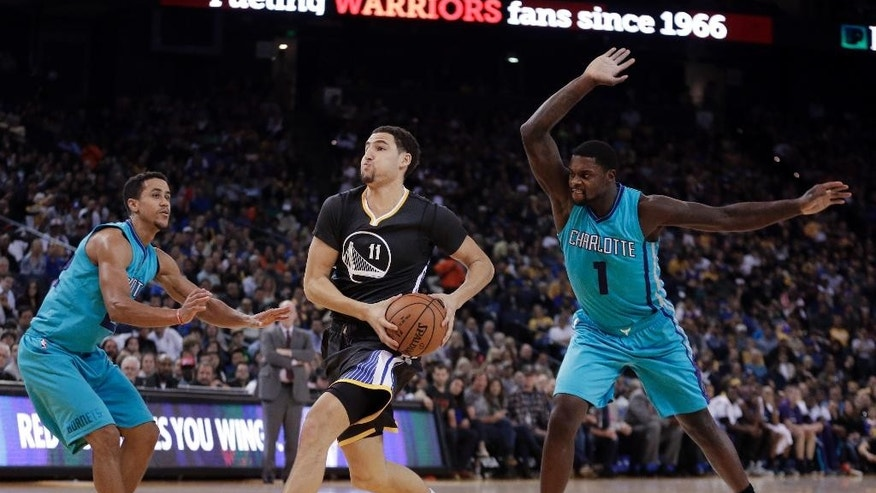 Golden State Warriors' Klay Thompson, center, drives the ball between Charlotte Hornets' Brian Roberts, left, and Lance Stephenson during the first half of an NBA basketball game Saturday, Nov. 15, 2014, in Oakland, Calif. (AP Photo/Ben Margot)