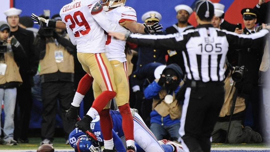 San Francisco 49ers cornerback Chris Culliver (29) and Eric Reid (35) celebrate after New York Giants tight end Larry Donnell (84) drops the ball in the end zone during the second half of an NFL football game Sunday, Nov. 16, 2014, in East Rutherford, N.J.  (AP Photo/Bill Kostroun)