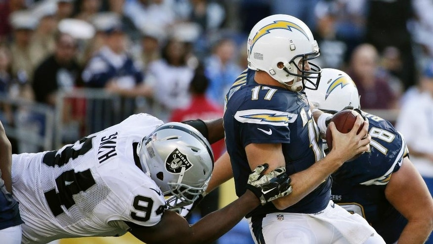 Oakland Raiders defensive tackle Antonio Smith drags down San Diego Chargers quarterback Philip Rivers for a sack during the second half of a NFL football game Sunday, Nov. 16, 2014, in San Diego. (AP Photo/Gregory Bull)