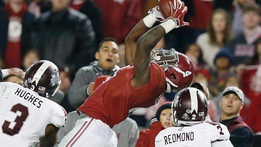 Alabama running back T.J. Yeldon (4) catches a pass against Mississippi State defensive back Jay Hughes (3) and Mississippi State defensive back Will Redmond (2) during the second half of an NCAA college football game Saturday, Nov. 15, 2014, in Tuscaloosa, Ala. (AP Photo/Brynn Anderson)