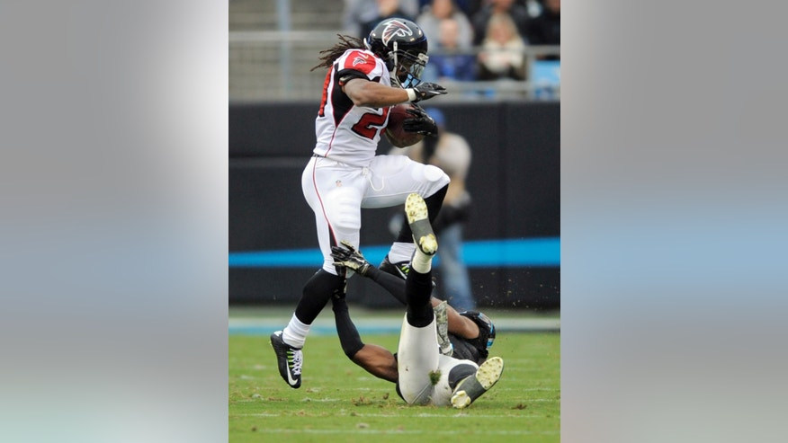 Atlanta Falcons' Devonta Freeman, top, hurdles Carolina Panthers' Roman Harper, bottom, in the second half of an NFL football game in Charlotte, N.C., Sunday, Nov. 16, 2014. (AP Photo/Mike McCarn)
