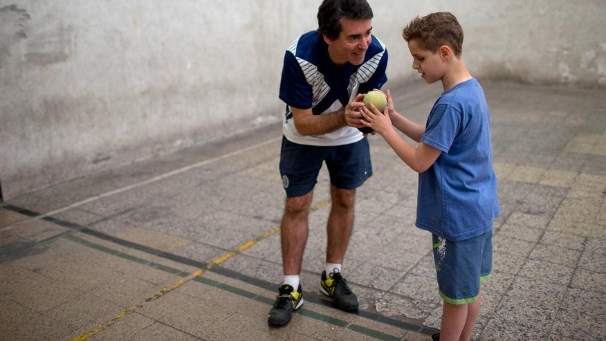 In this Nov. 12, 2014 photo, Eduardo Raffetto, director of Argentina Tennis Program for the Visually Impaired, left, has 9-year-old Felipe Angiono feel a special tennis ball made of foam and filled with metal pellets during his first class in Buenos Aires, Argentina. Played on a badminton-sized court with a lowered net and rope, players use junior tennis rackets and a ball that rattles upon impact. (AP Photo/Natacha Pisarenko)