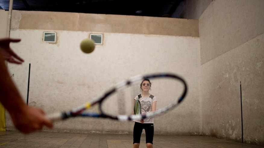 In this Nov. 12, 2014 photo, visually impaired tennis student Ludmila Mina, 15, prepares to return the ball as she trains with the Argentina Tennis Program for the Visually Impaired in Buenos Aires, Argentina. Played on a badminton-sized court with a lowered net and rope, players use junior tennis rackets and a foam ball filled with metal pellets that rattle upon impact. (AP Photo/Natacha Pisarenko)