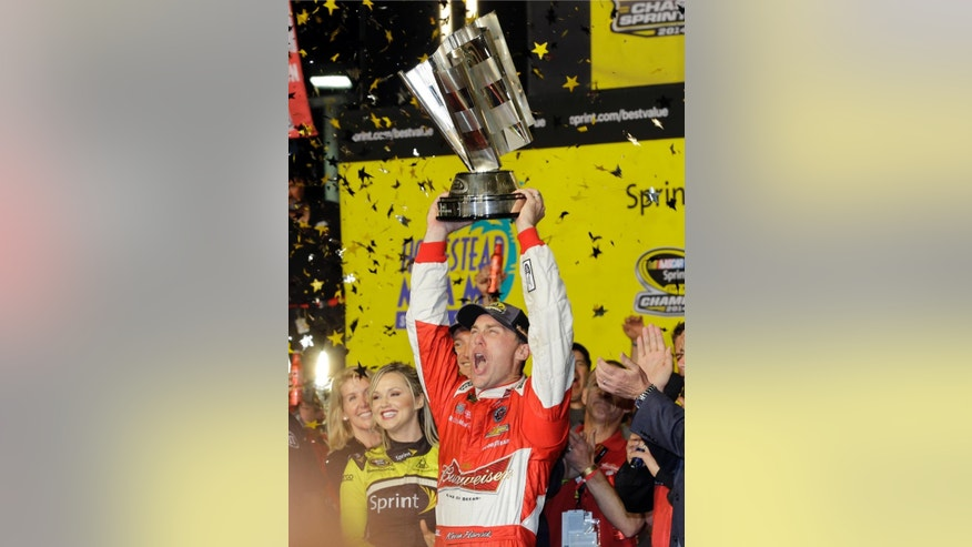 Kevin Harvick raises his trophy as he celebrates after winning the NASCAR Sprint Cup championship series auto race in Homestead, Fla., Sunday, Nov. 16, 2014. (AP Photo/Alan Diaz)