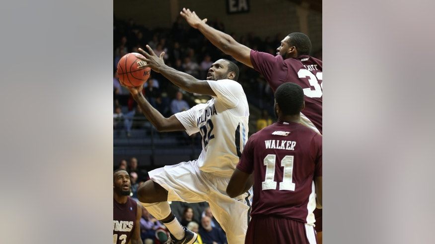 Villanova forward JayVaughn Pinkston (22) drives to the basket past Maryland-Eastern Shore's Dominique Elliott (32) and Devon Walker (11) in the second half of an NCAA college basketball game, Monday, Nov. 17, 2014, in Villanova, Pa. Villanova won 81-44. (AP Photo/Laurence Kesterson)