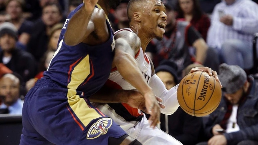 Portland Trail Blazers guard Damian Lillard, right, drives on New Orleans Pelicans guard Tyreke Evans during the first half of an NBA basketball game in Portland, Ore., Monday, Nov. 17, 2014.(AP Photo/Don Ryan)