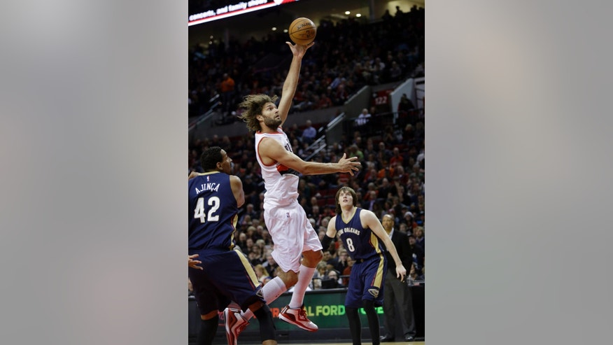 Portland Trail Blazers center Robin Lopez, middle, shoots between New Orleans Pelicans center Alexis Ajinca, from France, left, and forward Luke Babbitt during the first half of an NBA basketball game in Portland, Ore., Monday, Nov. 17, 2014.(AP Photo/Don Ryan)