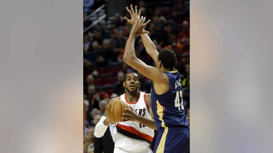 Portland Trail Blazers forward LaMarcus Aldridge, left, looks to shoot as New Orleans Pelicans center Alexis Ajinca, from France, defends during the first half of an NBA basketball game in Portland, Ore., Monday, Nov. 17, 2014.(AP Photo/Don Ryan)