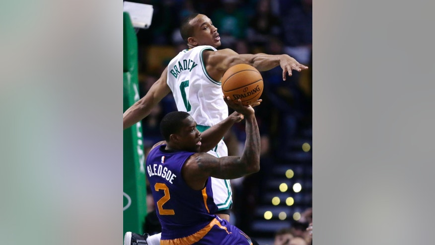 Boston Celtics guard Avery Bradley (0) tries to block a pass by Phoenix Suns guard Eric Bledsoe (2) during the first quarter of an NBA basketball game in Boston, Monday, Nov. 17, 2014. (AP Photo/Charles Krupa)