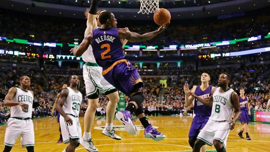 Phoenix Suns guard Eric Bledsoe (2) throws up a reverse lay-up after passing the Boston Celtics on a drive to the basket during the first quarter of an NBA basketball game in Boston, Monday, Nov. 17, 2014. (AP Photo/Charles Krupa)