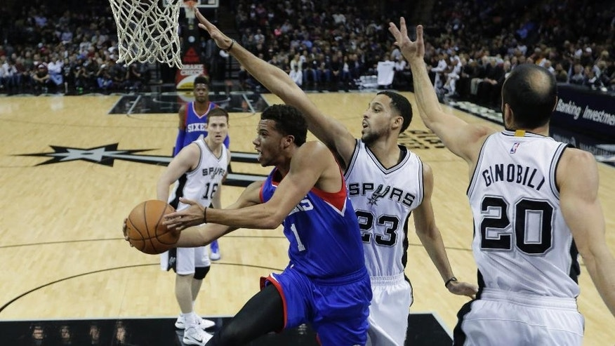 Philadelphia 76ers' Michael Carter-Williams (1) drives to the basket past San Antonio Spurs' Austin Daye (23) and Manu Ginobili (20) during the first half of an NBA basketball game, Monday, Nov. 17, 2014, in San Antonio, Texas. (AP Photo/Eric Gay)