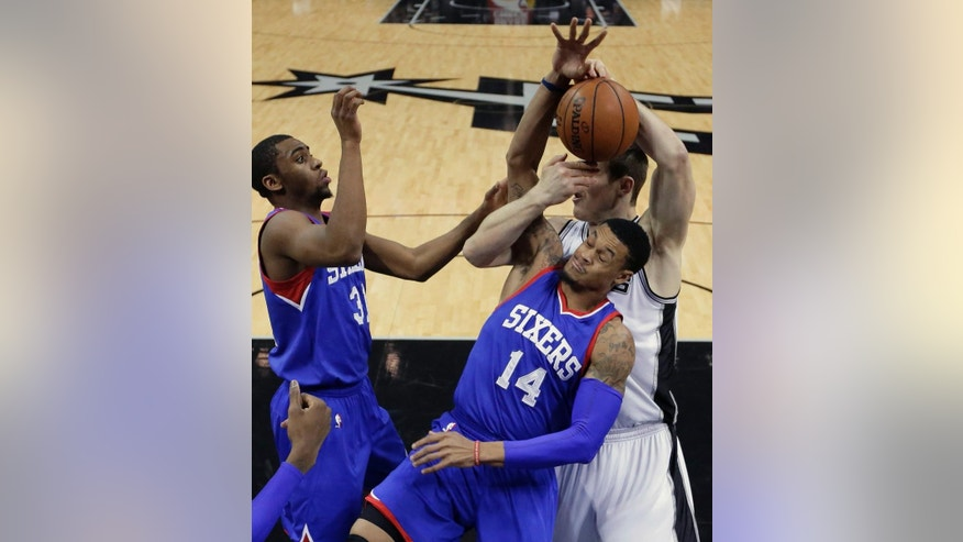 San Antonio Spurs' Aron Baynes, right, battles Philadelphia 76ers' K.J. McDaniels (14) Hollis Thompson (31) for a rebound during the first half of an NBA basketball game, Monday, Nov. 17, 2014, in San Antonio, Texas. (AP Photo/Eric Gay)