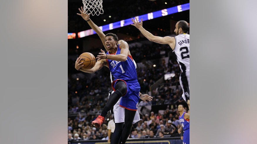 Philadelphia 76ers' Michael Carter-Williams (1) drives to the basket past San Antonio Spurs' Manu Ginobili (20) during the first half of an NBA basketball game, Monday, Nov. 17, 2014, in San Antonio, Texas. (AP Photo/Eric Gay)
