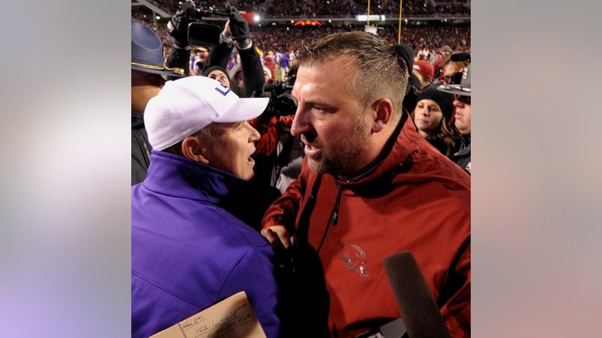 Arkansas coach Bret Bielema, right, shakes hands with LSU coach Les Miles after Arkansas defeated LSU 17-0 in an NCAA college football game in Fayetteville, Ark., Saturday, Nov. 15, 2014. (AP Photo/David Quinn)