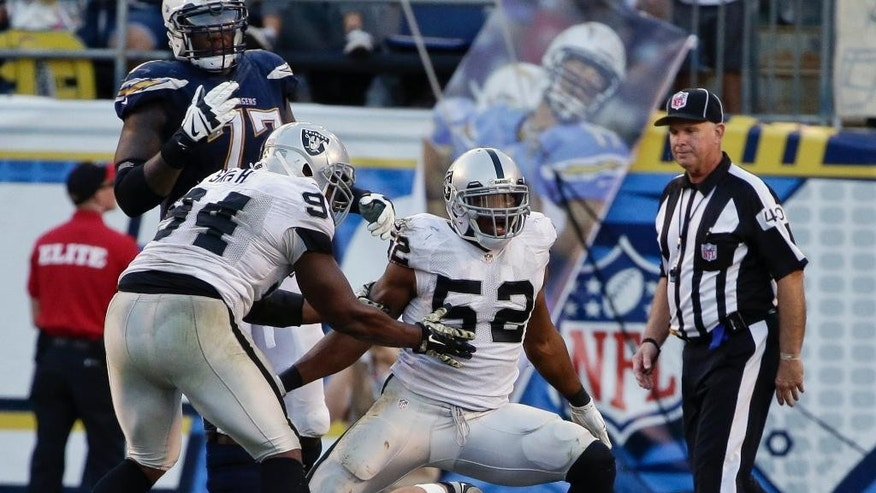 Oakland Raiders outside linebacker Khalil Mack, right, stands over San Diego Chargers quarterback Philip Rivers while celebrating his sack of Rivers during the second half of an NFL football game Sunday, Nov. 16, 2014, in San Diego. (AP Photo/Gregory Bull)