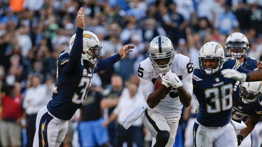 Oakland Raiders wide receiver Kenbrell Thompkins splits San Diego Chargers defenders while running with a pass reception during the second half of an NFL football game won 13-6 by the Chargers, Sunday, Nov. 16, 2014, in San Diego. (AP Photo/Gregory Bull)
