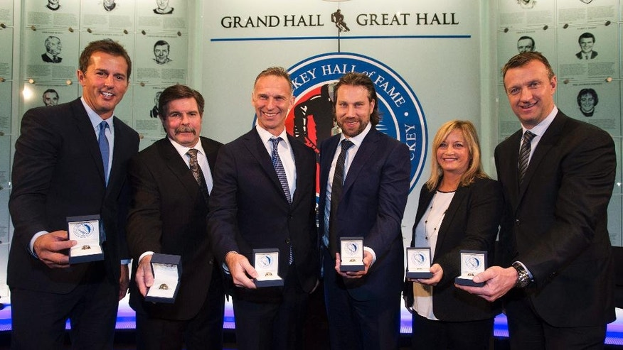 From left, Hockey Hall of Fame 2014 inductees Mike Modano, Bill McCreary, Dominik Hasek, Peter Forsberg, Lynn Burns, the wife of the late Pat Burns and Rob Blake pose for a photo at The Hockey Hall of Fame in Toronto Friday, Nov. 14, 2014. (AP Photo/The Canadian Press, Nathan Denette)