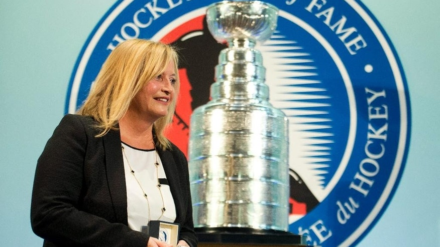 Lynn Burns, wife of the 2014 Hockey Hall of Fame inductee the late Pat Burns, walks by the Stanley Cup at The Hockey Hall of Fame in Toronto Friday, Nov. 14, 2014. (AP Photo/The Canadian Press, Nathan Denette)