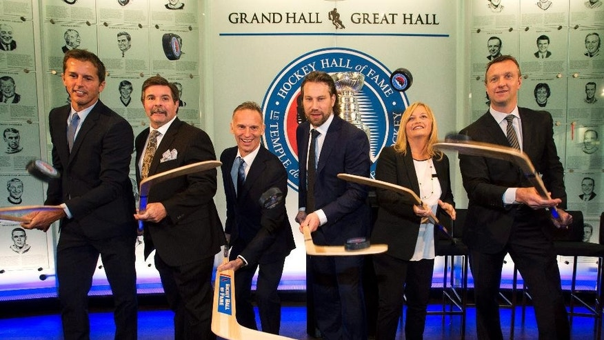From left, Hockey Hall of Fame 2014 inductees Mike Modano, Bill McCreary, Dominik Hasek, Peter Forsberg, Lynn Burns, the wife of the late Pat Burns and Rob Blake pose for a photograph at The Hockey Hall of Fame in Toronto Friday, Nov. 14, 2014. (AP Photo/The Canadian Press, Nathan Denette)