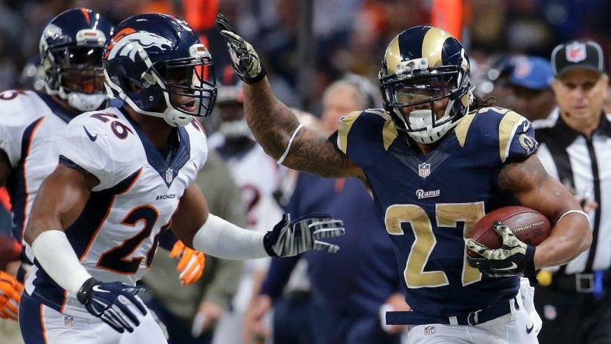 St. Louis Rams running back Tre Mason, right, runs past Denver Broncos free safety Rahim Moore on his way to a 27-yard gain during the second half of an NFL football game, Sunday, Nov. 16, 2014, in St. Louis. (AP Photo/Charlie Riedel)