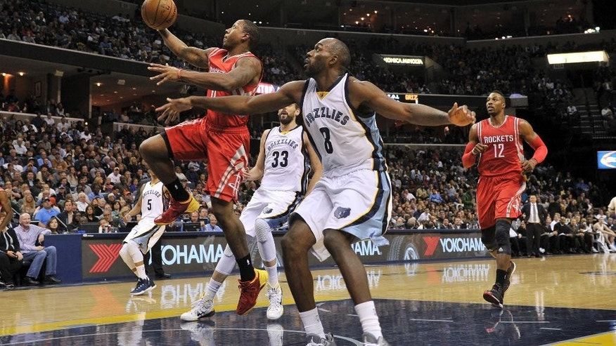 Houston Rockets guard Isaiah Canaan (0) drives past Memphis Grizzlies center Marc Gasol (33) and guard Quincy Pondexter (8) in the first half of an NBA basketball game Monday, Nov. 17, 2014, in Memphis, Tenn. (AP Photo/Brandon Dill)