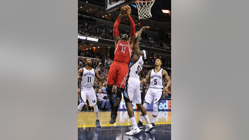 Houston Rockets center Dwight Howard (12) shoots against Memphis Grizzlies forward Zach Randolph (50), guard Mike Conley (11) and guard Courtney Lee (5) in the first half of an NBA basketball game Monday, Nov. 17, 2014, in Memphis, Tenn. (AP Photo/Brandon Dill)