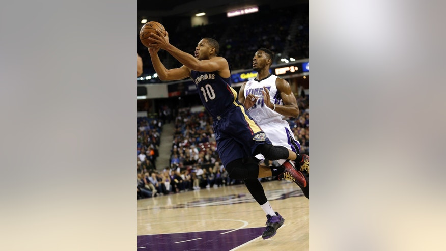 New Orleans Pelicans guard Eric Gordon, left, goes up for a shot past Sacramento Kings forward Jason Thompson during the first half of an NBA basketball game in Sacramento, Calif., Tuesday, Nov. 18, 2014. (AP Photo/Rich Pedroncelli)