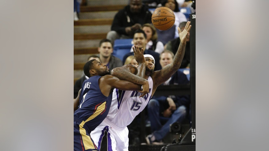 Sacramento Kings center DeMarcus Cousins, right, grabs a rebound against New Orleans Pelicans guard Tyreke Evans during the first half of an NBA basketball game in Sacramento, Calif., Tuesday, Nov. 18, 2014. (AP Photo/Rich Pedroncelli)