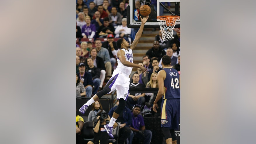 Sacramento Kings forward Rudy Gay, left, drives to the basket as New Orleans Pelicans center Alexis Ajinca, right, of France, looks on during the first half of an NBA basketball game in Sacramento, Calif., Tuesday, Nov. 18, 2014. (AP Photo/Rich Pedroncelli)