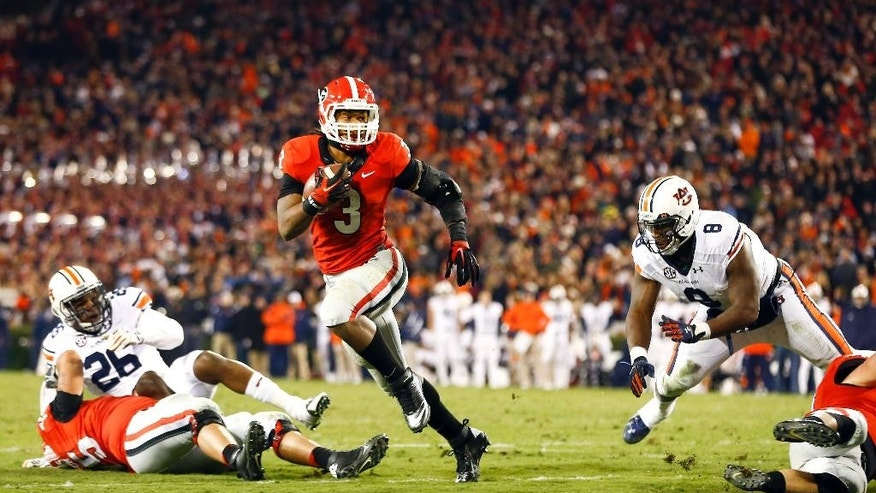 Auburn running back Cameron Artis-Payne (44) outruns Georgia defensive back Dominick Sanders (24) to score a touchdown in the first half of an NCAA college football game Saturday, Nov. 15, 2014, in Athens, Ga. (AP Photo/John Bazemore)