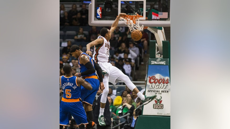 Milwaukee Bucks' John Henson dunks next to New York Knicks' Carmelo Anthony during the first half of an NBA basketball game Tuesday, Nov. 18, 2014, in Milwaukee. (AP Photo/Tom Lynn)