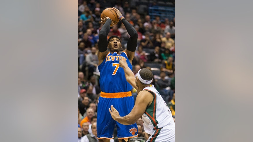 New York Knicks' Carmelo Anthony shoots over Milwaukee Bucks' Jared Dudley during the first half of an NBA basketball game Tuesday, Nov. 18, 2014, in Milwaukee. (AP Photo/Tom Lynn)