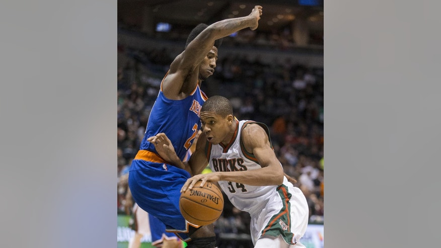 Milwaukee Bucks' Giannis Antetokounmpo drives against New York Knicks' Iman Shumpert during the second half of an NBA basketball game Tuesday, Nov. 18, 2014, in Milwaukee. (AP Photo/Tom Lynn)