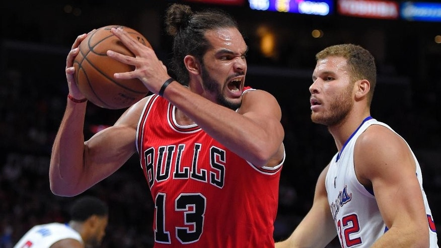 Chicago Bulls center Joakim Noah, left, grabs a rebound away from Los Angeles Clippers forward Blake Griffin during the first half of an NBA basketball game, Monday, Nov. 17, 2014, in Los Angeles.  (AP Photo/Mark J. Terrill)