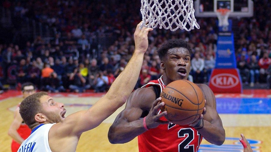 Chicago Bulls guard Jimmy Butler, right, puts up a shot as Los Angeles Clippers forward Blake Griffin defends during the first half of an NBA basketball game, Monday, Nov. 17, 2014, in Los Angeles.  (AP Photo/Mark J. Terrill)