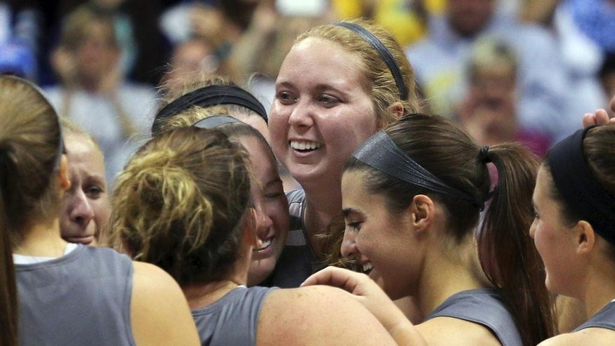 FILE - In this Nov. 2, 104 file photo, Mount St. Joseph's Lauren Hill, center, gets congratulated by teammates after scoring during her first NCAA college basketball game against Hiram University at Xavier University in Cincinnati. The freshman player is taking life day-to-day as a cancerous tumor in her brain grows. As part of her final push, Hill is raising money to research and treat the type of cancer that is taking her life. A big donation on Tuesday, Nov. 18, 2014, pushed the total raised to more than $324,000. (AP Photo/Tom Uhlman, File)