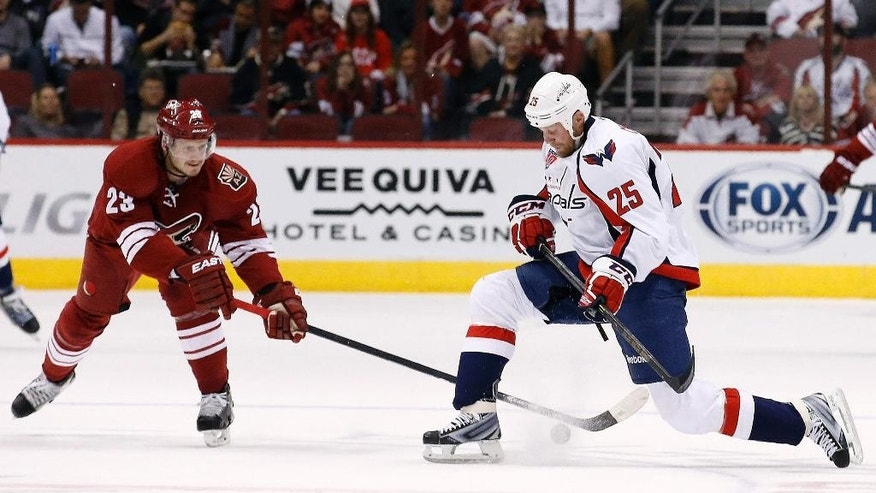 Washington Capitals' Jason Chimera (25) slides past the puck as Arizona Coyotes' Oliver Ekman-Larsson (23), of Sweden, tries to get a stick on the puck during the first period of an NHL hockey game Tuesday, Nov. 18, 2014, in Glendale, Ariz. (AP Photo/Ross D. Franklin)