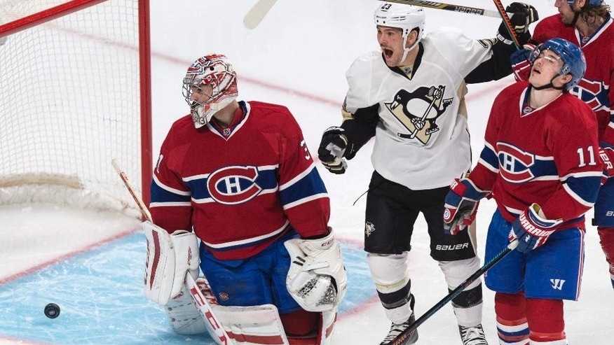 Pittsburgh Penguins' Steve Downie celebrates a goal past Montreal Canadiens goalie Carey Price, left, by teammate Brandon Sutter as Canadiens Brendan Gallagher (11) looks on during second period NHL hockey action Tuesday, Nov.  18, 2014 in Montreal. (AP Photo/The Canadian Press, Paul Chiasson)