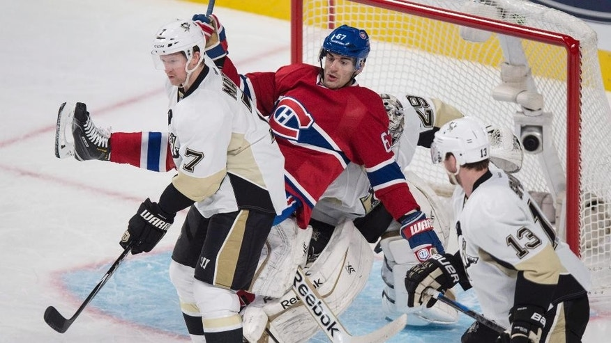 Montreal Canadiens' Max Pacioretty falls onto Pittsburgh Penguins goalie Marc-Andre Fleury in front of Penguins Paul Martin, left, and Nick Spaling during second period NHL hockey action Tuesday, Nov. 18, 2014 in Montreal. (AP Photo/The Canadian Press, Paul Chiasson)