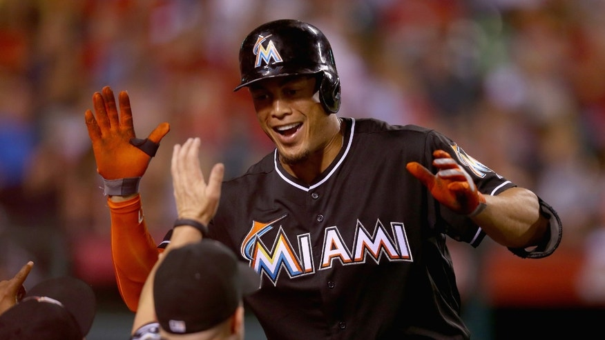 ANAHEIM, CA - AUGUST 25:  Giancarlo Stanton #27 of the Miami Marlins receives high fives in the dugout after hitting a three-run home run against the Los Angeles Angels of Anaheim in the fourth inning at Angel Stadium of Anaheim on August 25, 2014 in Anaheim, California.  (Photo by Jeff Gross/Getty Images)