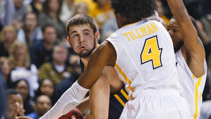 Toledo center Nathan Boothe ooks for help as Virginia Commonwealth forward Justin Tillman (4) and guard Jordan Burgess, right, defend during the second half of an NCAA college basketball game in Richmond, Va., Tuesday, Nov. 18, 2014. VCU won 87-78. (AP Photo/Steve Helber)
